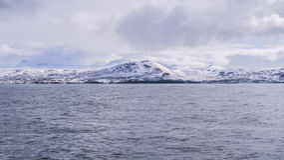 Acqua croccante di Icey del nevischio con una montagna di Snowy Immagine Stock