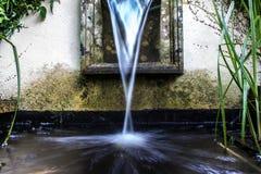 Acqua dalle terre di pietra della fontana in stagno Fotografie Stock Libere da Diritti