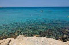 Acqua del turchese del mar Mediterraneo con le pietre, le barche e la costa Fotografia Stock Libera da Diritti