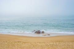 Acqua dell'oceano del mare della riva della spiaggia sabbiosa con le rocce e le pietre durante la nebbia Immagine Stock