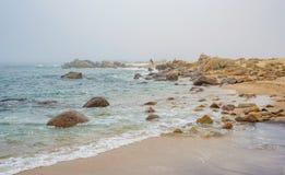 Acqua dell'oceano del mare della riva della spiaggia sabbiosa con le rocce e le pietre durante la nebbia Immagini Stock