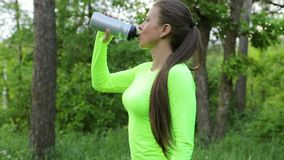 Acqua della bevanda della donna dopo lo sguardo della foresta di sport alla macchina fotografica e ai tumbs sorridenti di manifes stock footage