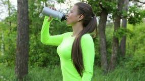 Acqua della bevanda della donna dopo lo sport nel più forrest video d archivio
