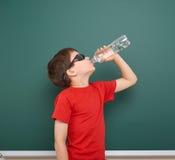 Acqua della bevanda dello scolaro dalla bottiglia vicino ad una lavagna, spazio vuoto, concetto di istruzione Fotografie Stock