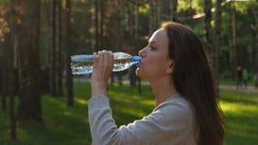Acqua della bevanda della donna in parco contro il sole di sera video d archivio