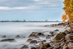 Acqua della linea costiera come nebbia e pietre Immagine Stock