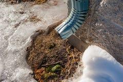 Acqua della sgocciolatura del tubo del metallo su neve di fusione Immagine Stock Libera da Diritti