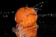 Acqua della spruzzata del mandarino sullo specchio nero del fondo Fotografie Stock