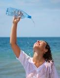 Acqua della spruzzata della ragazza sopra lei dalla bottiglia Immagine Stock