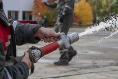 Acqua dello spruzzo dei pompieri durante l'esercizio di allenamento immagine stock libera da diritti