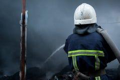 Acqua dello spruzzo dei pompieri Fumo e buiding dopo il fuoco Fotografia Stock