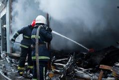 Acqua dello spruzzo dei pompieri Fumo e buiding dopo il fuoco Immagini Stock Libere da Diritti