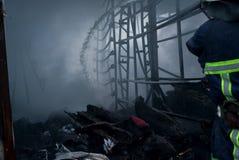 Acqua dello spruzzo dei pompieri Fumo e buiding dopo il fuoco fotografie stock