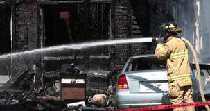 Acqua dello spruzzo del pompiere con il tubo flessibile sulla casa bruciata video d archivio