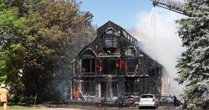 Acqua dello spruzzo del pompiere sulla casa con il camion di scala archivi video