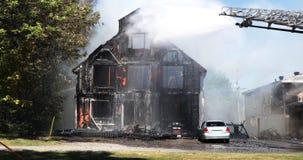Acqua dello spruzzo del pompiere sulla casa con il camion di scala video d archivio