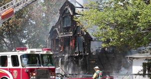 Acqua dello spruzzo del pompiere sulla casa con il camion di scala stock footage