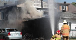 Acqua dello spruzzo del pompiere sulla casa con il tubo flessibile video d archivio