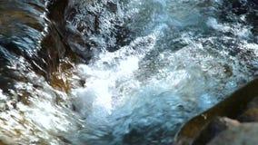 Acqua di fiume rapida che scorre fra le grandi pietre che creano schiuma di ribollimento bianca Corrente dell'acqua che scorre fr stock footage