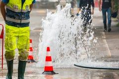 Acqua di getto della strada accanto ai coni di traffico e ad un tecnico Fotografie Stock Libere da Diritti