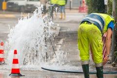 Acqua di getto della strada accanto ai coni ed al riparatore di traffico Immagini Stock