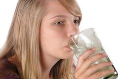 Acqua di ghiaccio bevente dell'adolescente da un vetro immagine stock
