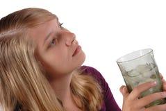 Acqua di ghiaccio di vetro della holding dell'adolescente che osserva via fotografie stock libere da diritti