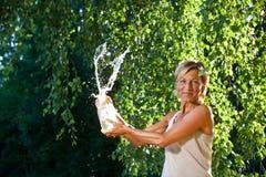 Acqua di lancio della donna sveglia nell'aria Fotografia Stock