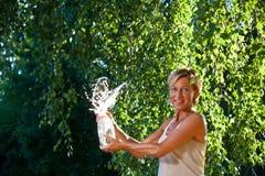 Acqua di lancio della donna sveglia nell'aria Fotografie Stock