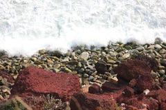 Acqua di mare che spruzza alla riva sulle rocce, sui ciottoli e sulle pietre rossi della spiaggia fotografie stock