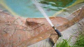 Acqua di nebbia della fucilazione del tubo flessibile di pressione di acqua nella recinzione del marinaio dello zoo stock footage
