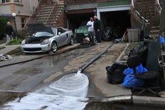Acqua di pompaggio della gente dal garage Fotografia Stock Libera da Diritti