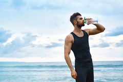 Acqua di rinfresco bevente dell'uomo dopo l'allenamento alla spiaggia bevanda Fotografie Stock