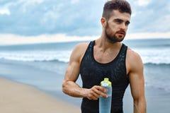 Acqua di rinfresco bevente dell'uomo dopo l'allenamento alla spiaggia bevanda Fotografie Stock Libere da Diritti