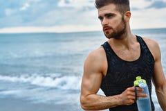 Acqua di rinfresco bevente dell'uomo dopo l'allenamento alla spiaggia bevanda Immagine Stock Libera da Diritti