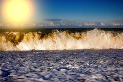 Acqua di rotolamento e retrocedere del mare nei raggi del tramonto immagine stock libera da diritti
