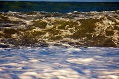 Acqua di rotolamento e retrocedere del mare nei raggi del tramonto fotografie stock libere da diritti