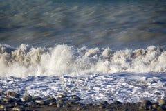 Acqua di rotolamento e retrocedere del mare nei raggi del tramonto fotografia stock libera da diritti