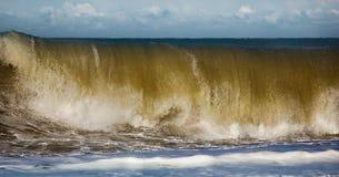 Acqua di rotolamento e retrocedere del mare nei raggi del tramonto fotografia stock