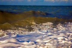 Acqua di rotolamento e retrocedere del mare nei raggi del tramonto immagini stock