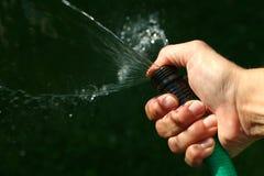 Acqua di spruzzatura con il tubo flessibile immagini stock