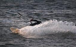 Acqua di spruzzatura del surfista dell'aquilone che fa un movimento Immagine Stock