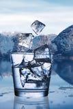 Acqua di versamento con ghiaccio in un vetro contro il paesaggio della natura fotografie stock libere da diritti