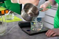 Acqua di versamento da una pentola in un vetro Fotografie Stock