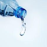 Acqua di versamento dalla bottiglia di acqua Immagini Stock Libere da Diritti