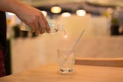 Acqua di versamento del cameriere dall'imbottigliare il vetro Fotografia Stock