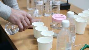 Acqua di versamento dell'uomo in un vetro eliminabile da una bottiglia di plastica video d archivio