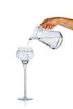 Acqua di versamento della mano dalla brocca di vetro Fotografia Stock