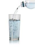 Acqua di versamento in vetro su fondo bianco Fotografia Stock