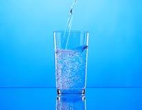 Acqua di versamento in vetro su fondo blu Fotografia Stock